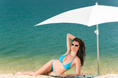 Summer beach woman blue bikini under parasol Royalty Free Stock Image