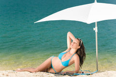 Summer beach woman blue bikini under parasol. Summer woman in bikini alone on beach sunbathing under parasol Stock Photos