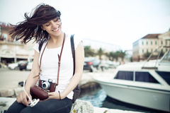 Summer beach woman fun holding vintage retro camera laughing and smiling happy during summer holiday vacation travel. Women sitting on sea deck near marine boat Stock Image
