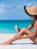 Summer beach woman putting sun protection sunblock. Sunscreen suntan lotion spray skincare product closeup of woman putting tanning oil on legs. Hand holding Royalty Free Stock Photos