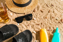 Summer beachwear, flip flops, hat, cold drink in a glass and seashells on sand beach. Royalty Free Stock Image