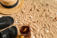 Summer beachwear, flip flops, hat, cold drink in a glass and seashells on sand beach. Stock Photo