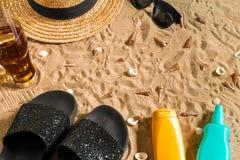 Summer beachwear, flip flops, hat, cold drink in a glass and seashells on sand beach. Stock Photos