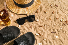 Summer beachwear, flip flops, hat, cold drink in a glass and seashells on sand beach. Royalty Free Stock Photos