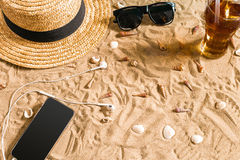 Summer beachwear, sunglasses, hat, cold drink in a glass and seashells on sand beach. Royalty Free Stock Photo