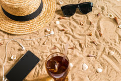 Summer beachwear, sunglasses, hat, cold drink in a glass and seashells on sand beach. Stock Photo