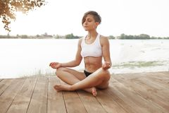 Summer. A beautiful girl with a short haircut practices yoga in the lotus position. Athletic woman meditating by the lake. Sportive people lifestyle royalty free stock photography