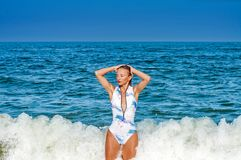 Summer. Beautiful tanned woman in swimsuit is coming out of the ocean. Summer vacation. Beautiful tanned woman in swimsuit is coming out of the ocean on tropical royalty free stock photos