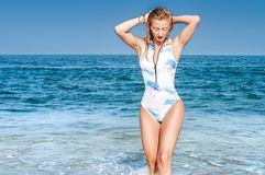 Summer. Beautiful tanned woman in swimsuit is coming out of the ocean. Summer vacation. Beautiful tanned woman in swimsuit is coming out of the ocean on tropical royalty free stock image