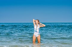 Summer. Beautiful tanned woman in swimsuit is coming out of the ocean. Summer vacation. Beautiful tanned woman in swimsuit is coming out of the ocean on tropical royalty free stock photography