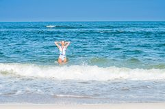 Summer. Beautiful tanned woman in swimsuit is coming out of the ocean. Summer vacation. Beautiful tanned woman in swimsuit is coming out of the ocean on tropical royalty free stock images