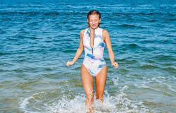 Summer. Beautiful tanned woman in swimsuit is coming out of the ocean. Summer vacation. Beautiful tanned woman in swimsuit is coming out of the ocean on tropical stock photography