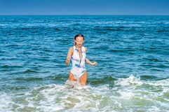 Summer. Beautiful tanned woman in swimsuit is coming out of the ocean. Summer vacation. Beautiful tanned woman in swimsuit is coming out of the ocean on tropical stock photos