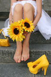 Summer Beauty. Yellow shoes and handbag behind at the feet of the bride, who is sitting and holding hands in sunflowers Royalty Free Stock Images