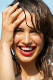 Summer Beauty. Beautiful happy tanned young woman outdoor in summer sun. Wet skin and hair covered in water. Red lipstick and natural makeup Royalty Free Stock Photo