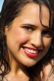 Summer Beauty. Beautiful happy tanned young woman outdoor in summer sun. Wet skin and hair covered in water. Red lipstick and natural makeup Royalty Free Stock Image