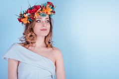 Beautiful Blonde Young Woman with Flowers Wreath, Long Curly Hair and Makeup on Blue Background stock image