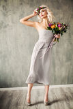 Summer Beauty Portrait of Beautiful Blonde Model Woman. With Blonde Hair, Blowing Dress and Flowers Royalty Free Stock Photo