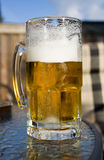 Summer Beer. Cold beer in glass with frothy head in sunshine atop a patio table during bbq Stock Photos