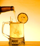 Summer Beer. Beer being poured into a mug with lemon Stock Photos