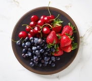 Summer berries in bowl on marble table, from above Royalty Free Stock Photography