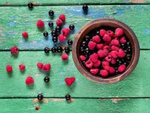 Summer berries in the bowl on old rustic wooden background. Stock Photos