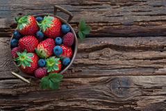 Summer berries in bowl. On wooden table, strawberry, raspberry and blueberry. Place for text Stock Images