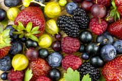 Summer berries by close up on a wooden background. Assortment of summer berries on a wooden dish Royalty Free Stock Images
