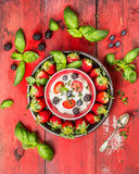 Summer berries with cottage cheese, basil leaves and spoon on red wooden background. Summer berries with cottage cheese, sugar, basil leaves and spoon on red Stock Image