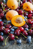 Summer berries and fruits: sweet cherries, blueberries and apric Royalty Free Stock Photos