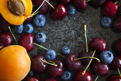 Summer berries and fruits. Sweet cherries, blueberries and apricots Royalty Free Stock Photo