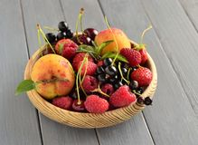 Summer berries and fruits in a wooden bowl Royalty Free Stock Photography