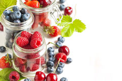 Summer berries in glass jar Stock Photos