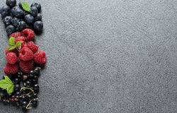 Summer berries on grey background. Raspberries, currants and blueberries on grey background. Copyspace above. Selective focus stock images