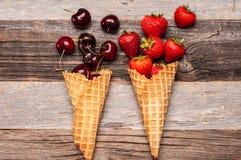 Summer berries in ice cream cones on wooden background. stock image