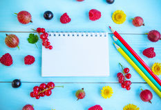 Summer berries, notepad and pencils Royalty Free Stock Photo