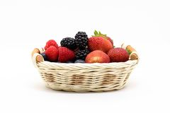 Summer berries in a wicker basket on a white background stock photography