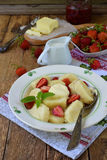 Summer berry breakfast. Sweet lazy pierogi, dumplings with sour cream, butter and strawberry on wooden background. Italian gnocchi Royalty Free Stock Image