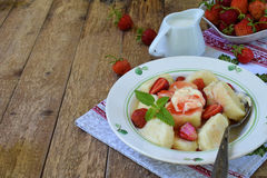 Summer berry breakfast. Sweet lazy pierogi, dumplings with sour cream, butter and strawberry on wooden background. Italian gnocchi Stock Photography