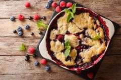 Summer berry cake with raspberry berries, currants and blueberries close-up in a baking dish. Horizontal top view royalty free stock photos