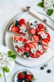 Summer Berry No Bake Cheesecake. Strawberry and Blueberry No Bake Cheesecake Decorated with Spring Flowers, copy space for your text stock photos