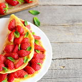 Summer berry omelette. Colorful easy omelette stuffed with fresh strawberries and garnished with mint on a plate. Recipes for kids. Healthy omelette. Kids stock photos