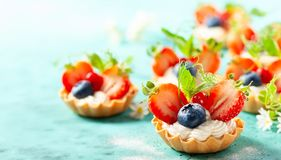 Summer berry tartlets  with cream and fresh berries royalty free stock photo