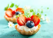 Summer berry tartlets  with cream and fresh berries royalty free stock images