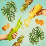 Summer beverages concept. Female hands holding bottles with splash smoothie or juice on blue background. With tropical leaves and fruits Stock Image