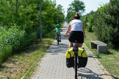 Summer bike trip. Two children on a bike trip with their mum on a summer sunny day royalty free stock photos
