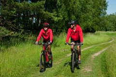 Summer bike - Young sportive couple in meadow. Summer - Young couple riding mountain bike  and wearing red clothes Stock Images
