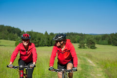 Summer bike - Young sportive couple in meadow. Summer - Sportive couple riding mountain bike in the nature Royalty Free Stock Image