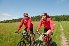 Summer bike - Young sportive couple in meadow. Happy couple riding mountain bike in summer meadow Stock Photos