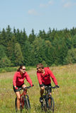 Summer bike - Young sportive couple in meadow. Sportive couple riding mountain bike in summer meadow on a sunny day Stock Image